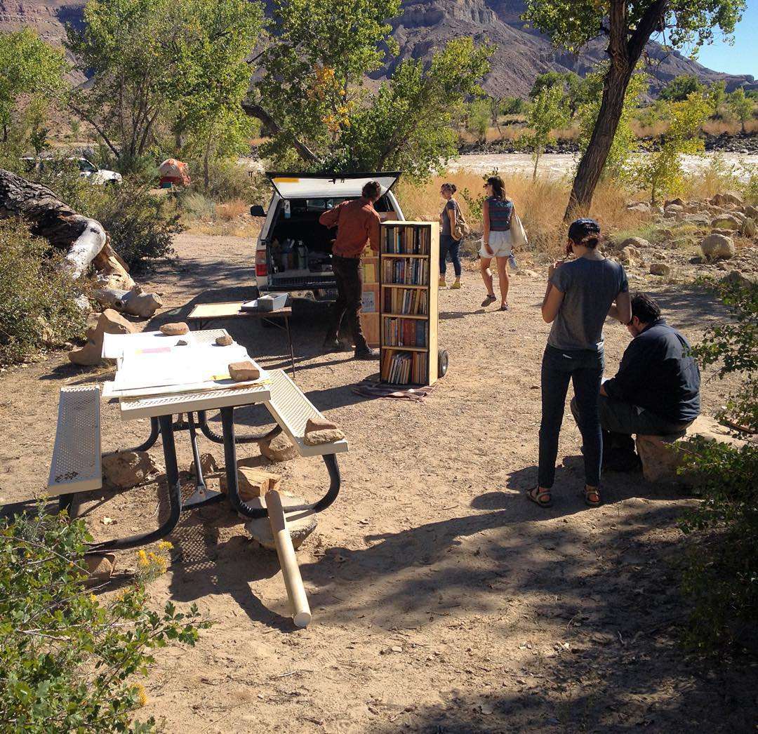 A library and readers sit on a picnic table and the back of a pickup truck next to a river in a redrock canyon.