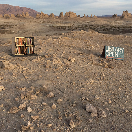 A library bookshelf in a desert landscape with tufa towers in the background.