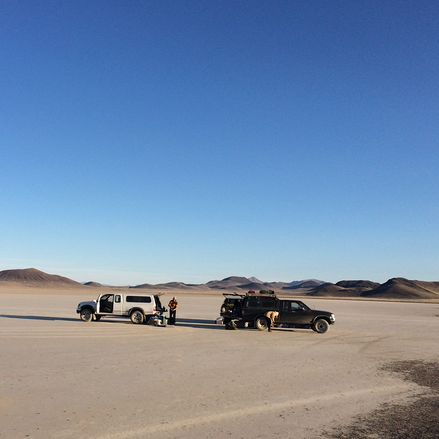 A circle of pickup trucks in the middle of a dry lakebed.