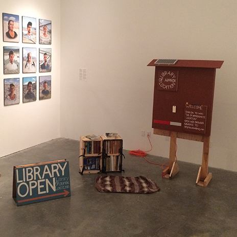 A library bookshelf, open sign, and interpretive sign sit in a gallery.